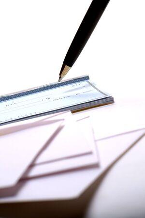 settlement: Pen hovering over a checkbook behind a stack of enveloppes