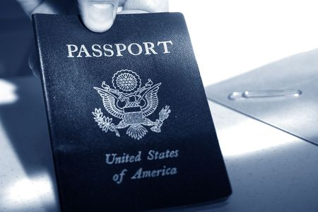 Male hand holding an American passport in blue tone color