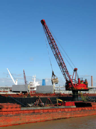 unloading: Heavy port crane with scooper unloading a barge