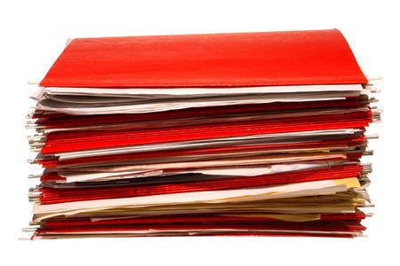 Pile of red hanging file folders filled with old papers isolated on white