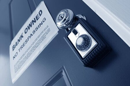 Real estate combination lock box on house door with bank owned foreclosure notice photo
