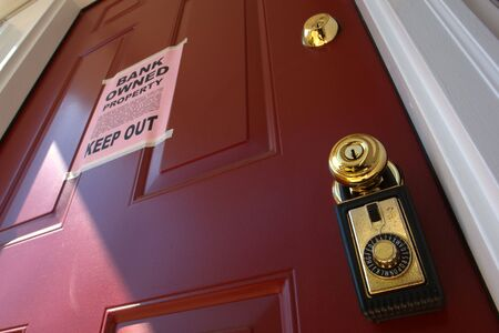Real estate lock box and bank owned keep out foreclosure notice on house door photo