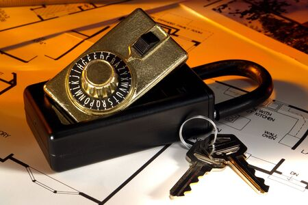 Real estate combination lock box with house keys over floor plans photo