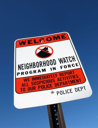 American residential neighborhood crime watch warning sign over blue sky Banque d'images