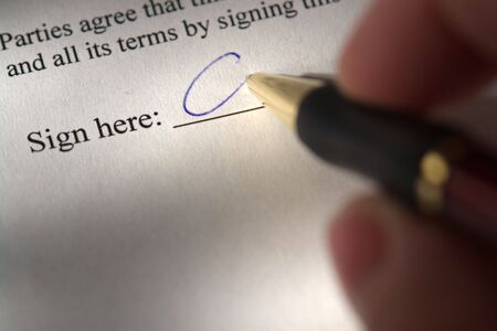 Fingers holding a pen while signing a document Stock Photo - 3003567