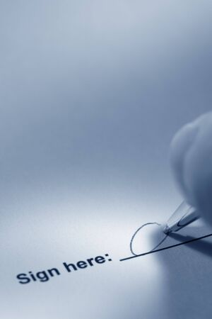 Fingers holding a pen while signing a document in blue tone color Stock Photo - 3003566