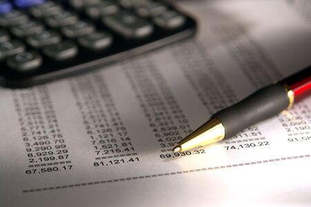 Ballpoint pen and calculator over financial statement with numbers