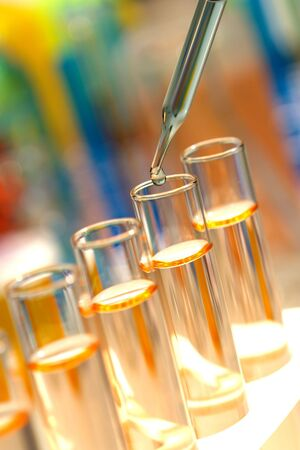 Pipette with drop over test tubes in a research lab Stock Photo - 3093568