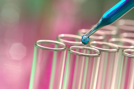 drug discovery: Pipette with emerging drop over test tubes in a research lab