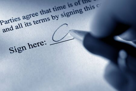 Fingers holding a pen while signing a contract