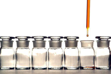 material de vidrio: Pipetear con las nuevas gota de l�quido en botellas de productos qu�micos en un laboratorio de investigaci�n Foto de archivo