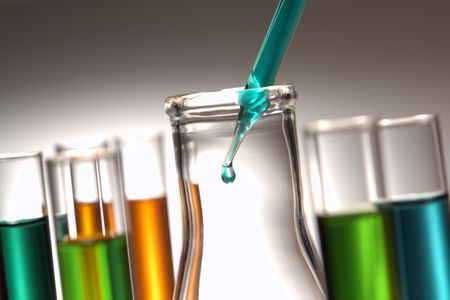 Pipette with emerging drop of liquid over Erlenmeyer flask in a research lab