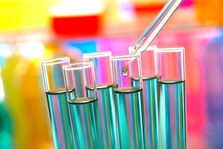 Pipette with emerging drop of liquid over test tubes in a research lab