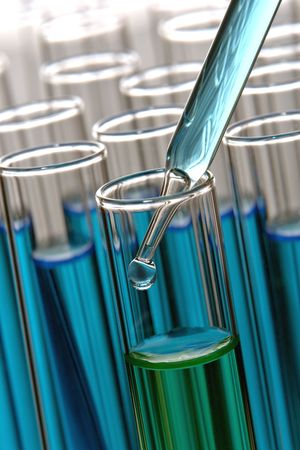 Pipette with emerging drop of liquid over test tubes in a research lab Stock Photo - 3459288