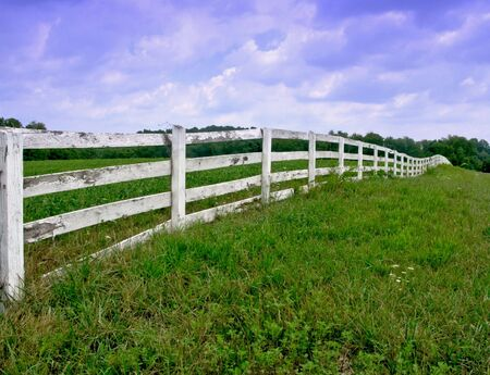 White wood fence in a field in the country