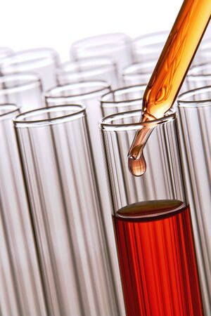 drug discovery: Pipette with emerging drop of liquid over test tubes in a research lab