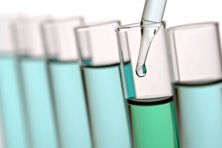 Pipette with emerging drop of liquid over test tubes in a science research lab Stock Photo
