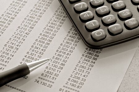 Ball point pen and calculator over financial statement with columns of numbers Stock fotó