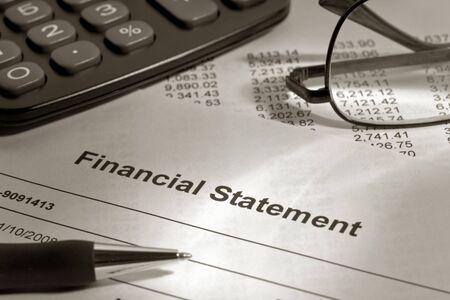 makelaardij: Balpen, glazen en rekenmachine over financieel memorandum Stockfoto