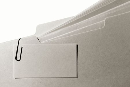 card file: Blank business card clipped with a paper clip to a manila tab file folder filled with paper