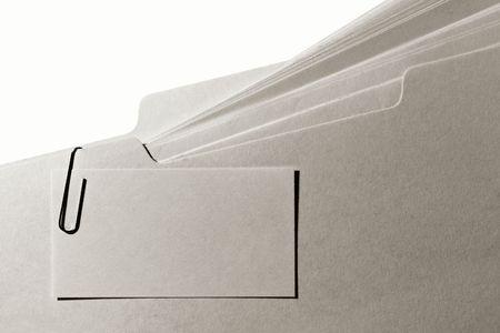 carpetas: Tarjeta de visita en blanco cortado con un clip de papel manila a una ficha carpeta llena de archivos con papel Foto de archivo