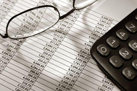 Spreadsheet met financiële cijfers met de rekenmachine en glazen
