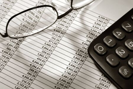 Spreadsheet with financial figures with calculator and glasses Banco de Imagens