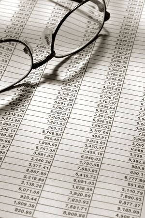 Spreadsheet met financiële cijfers met glazen Stockfoto