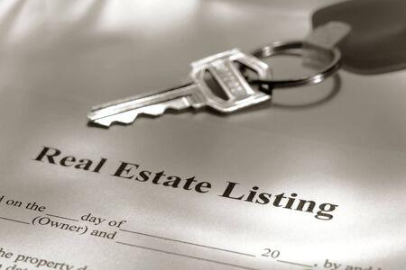 listing: Listado de Propiedades Inmobiliarias en contrato y clave en un llavero Foto de archivo
