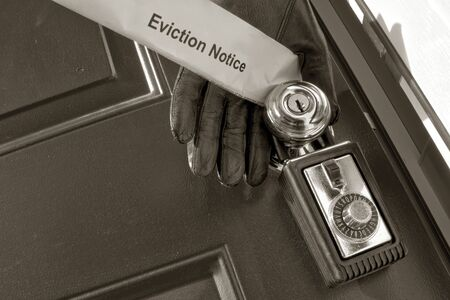 eviction: Sheriffs hand with leather glove opening a house door and holding an eviction notice