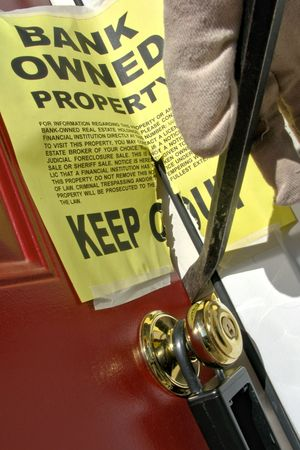 repossession: Gloved hand with crow bar breaking open a house door with bank owned foreclosure notice for repossession