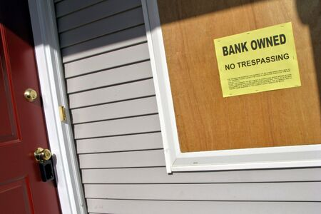 Bank owned sign posted on a boarded up house in Foreclosure photo