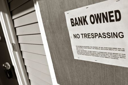 owned: Bank owned sign posted on a boarded up house in Foreclosure Stock Photo