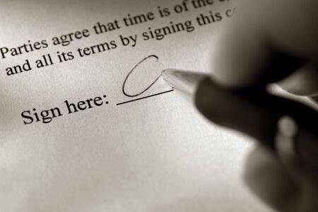 Fingers holding a pen and signing a contract on the signature line Stock Photo - 3883146