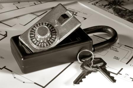 lockbox: Real estate combination lock box with house keys over floor plans