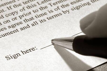 firmando: Dedos la celebraci�n de una pluma y la firma de un documento sobre la l�nea de la firma Foto de archivo