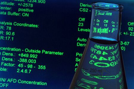 erlenmeyer: Glass Erlenmeyer flask and experiment data screen in a research lab Stock Photo