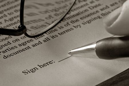 Fingers holding a pen and signing a contract document Stock Photo - 4082490