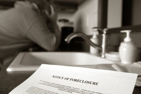 Foreclosure notice on kitchen counter with man holding his head in his hands