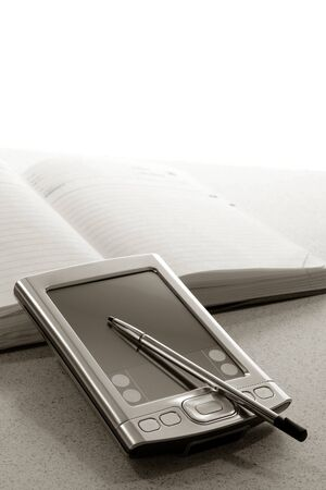 Handheld Personal Digital Assistant with no trademark markings and traditional appointment daily planner book