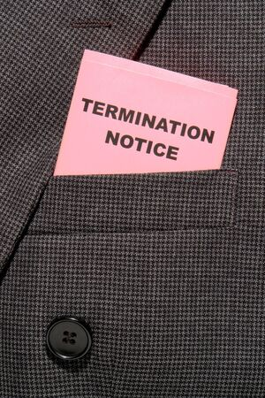 severance: Pink slip termination notice folded in an executive business man suit pocket Stock Photo