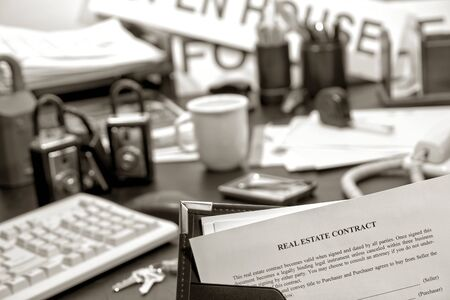 lockbox: Real estate home sale contract in a binder on busy Realtor desk in realty agent office (fictitious document)