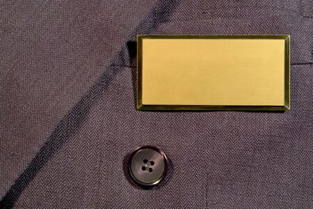 Blank gold and brass name tag on business man suit jacket pocket