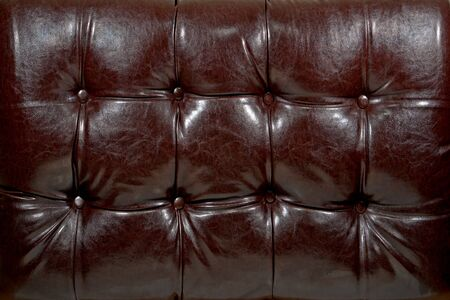 Padded furniture shiny brown leather like vinyl background Stock Photo