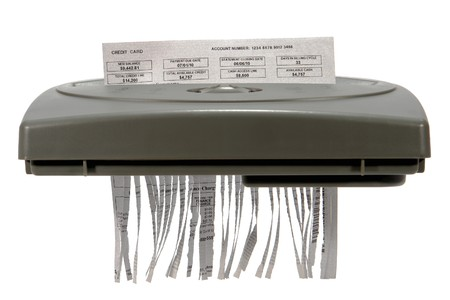 Credit card statement shredding in a paper shredder isolated on white (fictitious document) photo