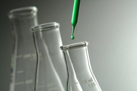 科学研究室で実験のため三角フラスコに液体の滴とピペットします。
