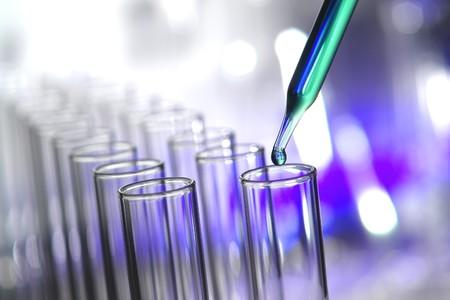 Pipetteer met druppel vloeistof over reageerbuizen voor een experiment in een wetenschappelijk onderzoek lab Stockfoto