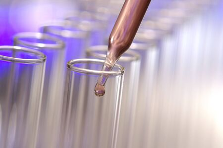 Pipette with drop of liquid over test tubes for an experiment in a science research lab photo