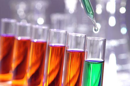 Pipetteer met druppel vloeistof over reageerbuizen voor een experiment in een wetenschappelijk onderzoekslaboratorium