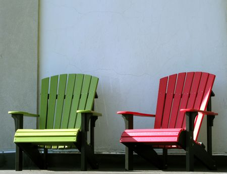 Two Bright Color Adirondack Resin Chairs On A Porch Photo